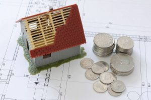 a miniature of a house and coins